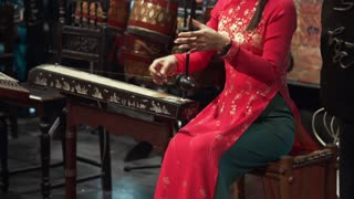 Asian woman in national dress plays on the one string folk instrument of her country, folk music, instrumental ensemble, muscial people, folk music concert, cultural roots