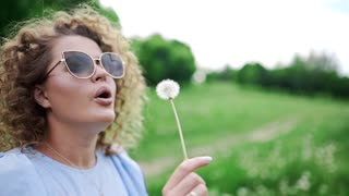 Attractive woman in sun glasses blows the dandelions and they fly away on the wind, beautiful kinky girl blows the dandelions to the wind, resting at the green park in summer sunny day