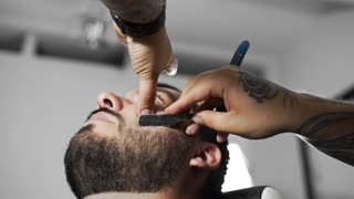 Barber shaves customer with straight razor blade, man's haircut and shaving at the hairdresser, barber shop and shaving salon