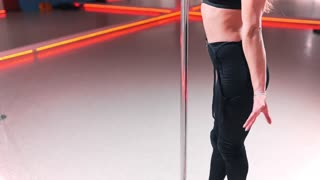Beautiful attractive white pole dancer in tight-fitting dress, woman with sexy shape is dancing near the pole, erotic dancing, choreography and qymnastics, exotic pole dance