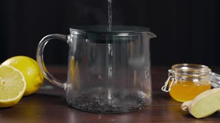 Boiling water is poured to the teapot with black tea, vitamin tea with lemon, ginger and honey, drink against sickness, hot drinks