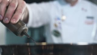 Chef adds olive oil to the dish, cooking in slow motion, falling liquid in 240 frames per second, cooking food