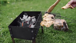 Chef makes BBQ with chicken wings on the hot coals of the grill outdoors, barbecue at the backyard
