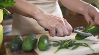 Chef peels cucumbers fof making vegetable salad with fresh greens, vegetarian dishes, cooking food, healthy nutrition