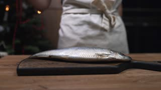 Chef puts herring fish to the wooden board and prepares for cooking, making of fish meals, dishes with fish, food cooking in the kitchen, s