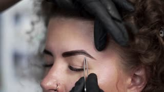 Correction of eyebrows shape by depilation by tweezers at the beauty salon, eyebrow coloring with henna and correction, beauty and healthcare, cosmetic services