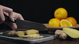 Ginger is sliced by sharp knife on the rock board, slices of fresh ginger, vegetables and vitamins, vegetarian diet, making of vitamin drink against illness