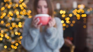 Happy smiling woman in the sweater drinks hot chocolate near the shining christmas tree at her living room, christmas eve, home comfort and New Year's mood, warming drink, pretty attractive woman