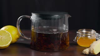 Hot black tea is brewed in the glass teapot, vitamin tea with lemon, ginger and honey, drink against sickness, hot drinks