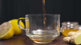 Hot black tea is poured to the glass cup, vitamin tea with lemon, ginger and honey, drink against sickness, hot drinks