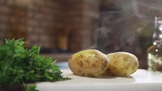 Hot boiled potatoes on the kitchen board, hot steam, boiled vegetables, dish with potatoe, cooking food