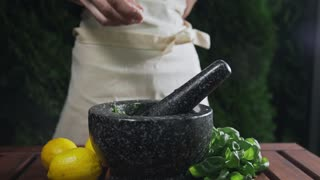 Housewife adds salt to the grinder with natural sauce, cooking food, spicy food, vegetarian meal, greens and salads, cooking outdoors