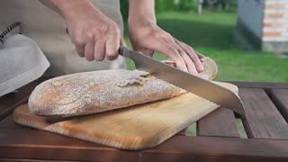Housewife cuts the baguette in a half by knife on the wooden board outdoors, flour and bakery, making the sandwitches