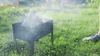 Man adds liquid ignition to the small smoking wood in the grill and flame bursts out, BBQ at the backyard, making hot coals for the cooking on the open fire, summer barbecue