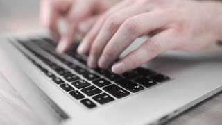 Man in gray pullover works with his notebook, man's hands type on the keyboard, man uses notebook, close up of hands with notebook, searching the internet, social media, e-commerce and buisness