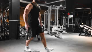 Man is pumping muscles at the gym, strength exercises, athlete at fitness club, caucasian man with beard is pumping muscles, guy with fit body and big muscles, health and beauty