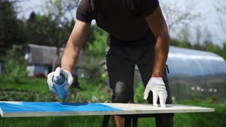 Man's hand in working glove sprays paint with spray can to the wooden surface outdoors, man paints the DIY furniture at his garden, hand made stuff