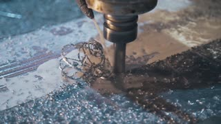 Milling machine cuts down the metal shavings from the workpiece, metalworking at plant, cutting out complex shapes in metal
