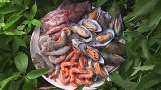 Raw mussles squid and prawns are on the board in the greens outdoors, meals with fish, seafood dish, roasted and grilled fish, preparations for barbecue, grill and fire, asian cuisine meals
