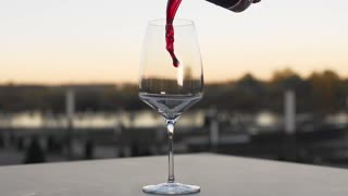 Red wine is poured to the wineglass outdoors in slow motion, bar and restaurant, alcohol drinks, food in slow motion, 240 frames per second