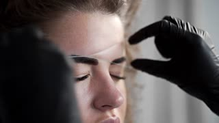 Removing small hairs from face with thread in beauty salon, depilation with thread, threading in beauty salon, facial treatment, cosmetic manipulation