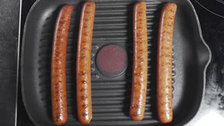 Sausages is roasting on the grill pan, sausage for hot dog, grilled meat, fast food kitchen, cooking at home, meals for lunch
