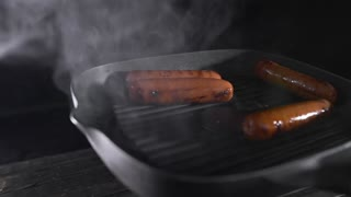 Sausages is roasting with smoke on the hot grilling pan, cooking food, meat meals, tasty food, chef at the kitchen, fast food, food in slow motion