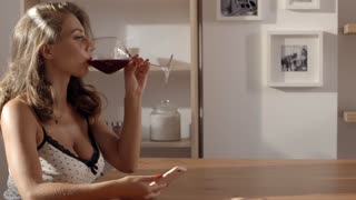 Sexy and attractive woman in candid dress is sitting in the cafe and drinks red wine from glass in her hand, charming beautiful woman with big brest and pretty face
