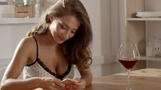 Sexy and attractive woman in candid dress sits at the table in a cafe with glass of red wine and texting on her smartphone with smile, attractive woman is alone in bar, woman texts to her boyfriend