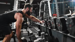 Strong man is pumping muscles at the gym, power exercises with dumbbells, athlete at fitness club, caucasian man with beard is pumping biceps