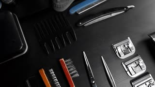 Stylish equipment table with scissors and trimmers and dark scull at the barber shop, making of haircuts, straight razor on the table, shaving salon