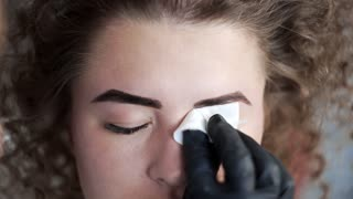 Stylist wipes eyebrows with a sponge after eyebrow coloring at the beauty salon, eyebrow coloring and correction, coloring with henna, beauty and healthcare, cosmetic services