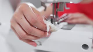 Tailor sews lingerie on a sewing machine, thread and lace, handmade underwear and clothes, sewing machine at work process, work in a sewing studio