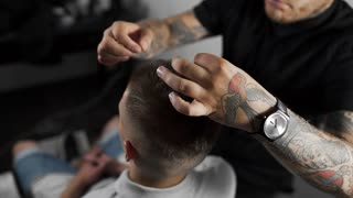 Tattoed barber makes hair styling with hair gel for customer after haircut at the barber shop, man's haircut and shaving at the hairdresser, barber shop and shaving salon