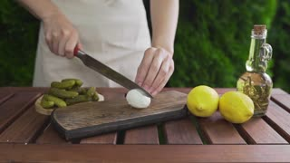 The cook cuts boiled egg in a half on the wooden board outdoors, cooking outside, appetizer from boiling eggs, stuffed eggs