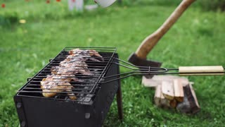 The cook makes BBQ on the hot coals of the grill outdoors and adds sauce to the crispy crust of chicken wings, barbecue at the backyard