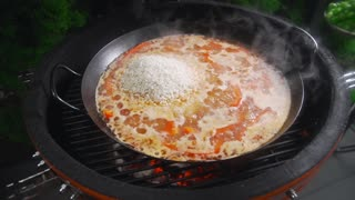 The cook makes paella on the open fire and adds green pea to the other ingredients in the big hot pan, grill anf barbecue, spanish food, paella with seafood, food cooking outdoors