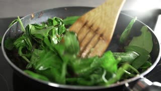 The cook makes vegetable dish with onion fried in balsamic vinegar and adds spinach
