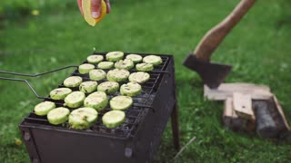 The cook makes vegetarian barbeque with zucchini in green onion sauce on the hot grill and squeezes lemon juice to it, BBQ at the backyard in the green summer day, cooking outdoors on the open fire in