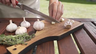 The cook slices garlic on the wooden board by sharp knife outside, cooking outside, cooking healthy food, summer meals