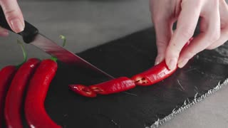 The cook slices hot chili peppers on the board, spicy food, meals with vegetables, vegetarian food, cooking at home
