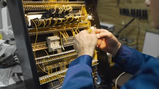 The electrician crimps the wires and wires them in a circuit in the instrument panel, works with high voltage, production of electrical control units, electric wiring