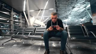 Traveler waits his flight at the waiting hall of the airport, man travels by air, man stares at the mobile phone screen, lonely passenger in the waiting hall