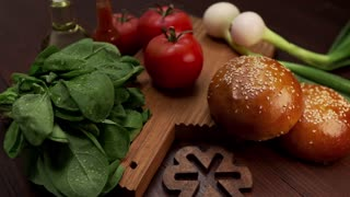 Video shows ingredients for making delicious burgers, fresh greens and vegetables for cooking, buns with sesame, cooking burgers, fastfood recipes, cooking at home