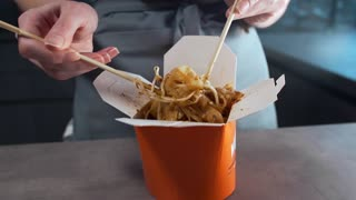 Woman mixes asian noodles in a box by chopsticks, panasian kitchen, fried noodles with seafood, spicy meals, WOK