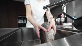 Woman prepaers fish for the cutting and making dish at the kitchen, sea and ocean food, river fish, meals with fish, chineese cuisine