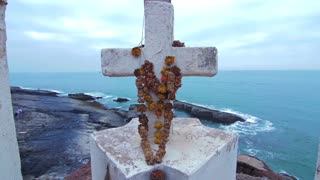 White cross with flowers on the hill at the ocean coast