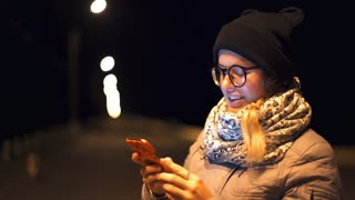Woman gets phone call in her smartphone in night time outdoors, gadgets in people's life, wireless communications, emotions by phone