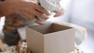 Woman packs gifts for new year, christmas presents for children, plaster figures in christmas box