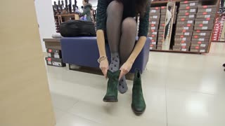 Woman trying on a pair of green suede shoes in a shoe store